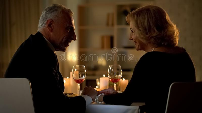 Beautiful aged lady looking at man, couple relaxing in restaurant, romantic date stock photos
