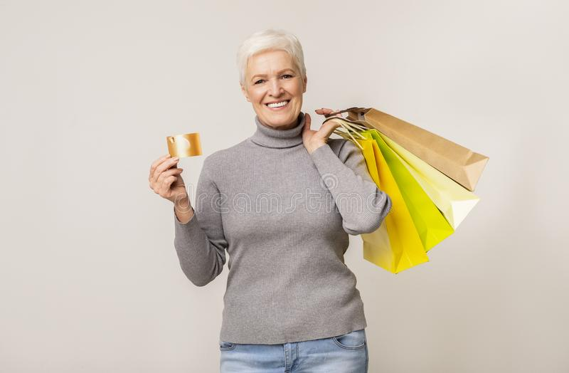 Beautiful aged lady with shopping bags and credit card royalty free stock images