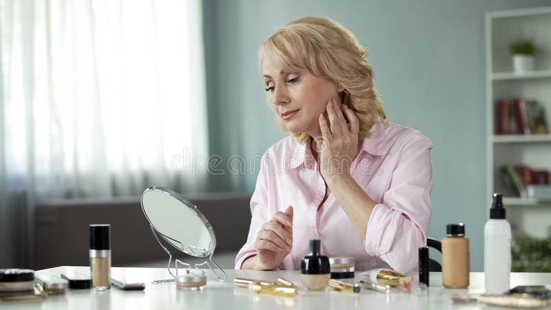 Beautiful aged woman touching her face, looking in mirror on table, make-up. Stock photo stock photos
