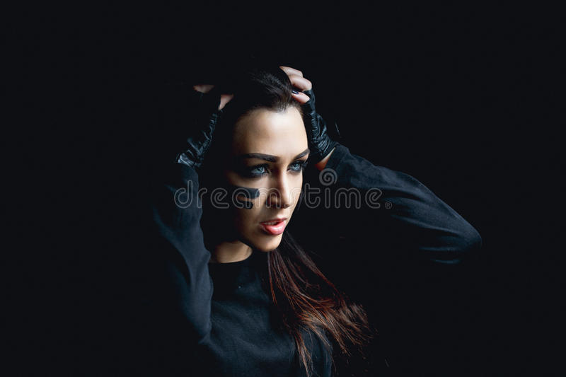 Beautiful aggressive woman over dark background. Dark and mysterious a pretty girl stands in shadow with camoflauge paint royalty free stock photos