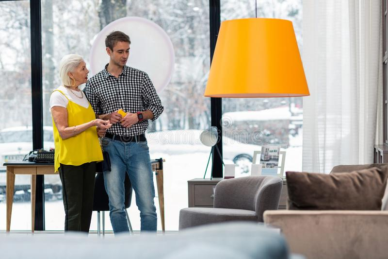 Beautiful aging mother choosing new furniture with attractive brown-haired son stock images