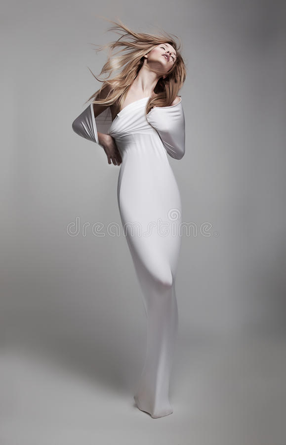 Beautiful airy young girl in white clothes. Luxurious mystical young woman in white clothes with waving long hair gracefully posing royalty free stock photography