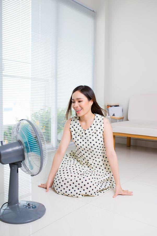 Beautiful aisan woman sitting on living room floor enjoying electric fan cool wind. royalty free stock photo