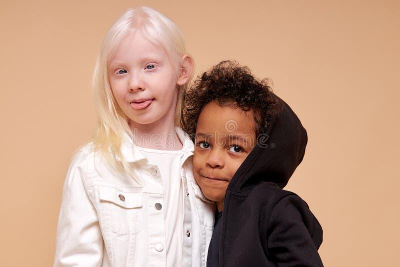 Beautiful albino girl with little multiracial boy isolated. Beautiful albino girl with little afro multiracial boy isolated, girl hug her black friend. girl show royalty free stock photo