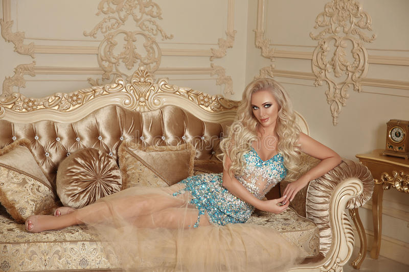 Beautiful alluring gorgeous woman in fashion dress lying on mode royalty free stock images