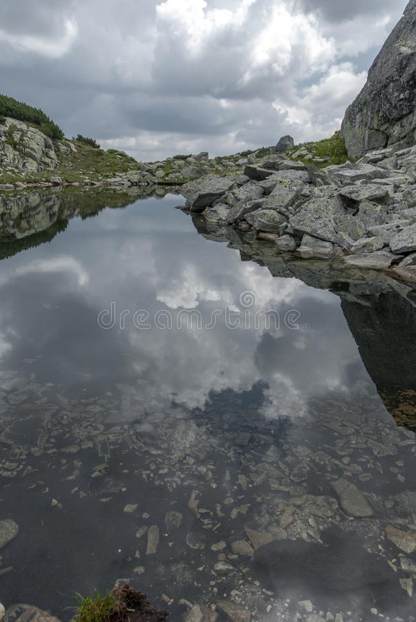 Beautiful alpine lake poster, mirror for the clouds. In Retezat Mountains, Romania stock images