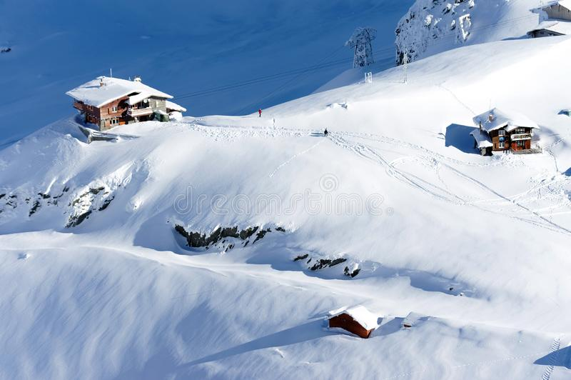 Beautiful alpine landscape with chalets, snow, sun and shadows in the Carpathians Mountains stock image
