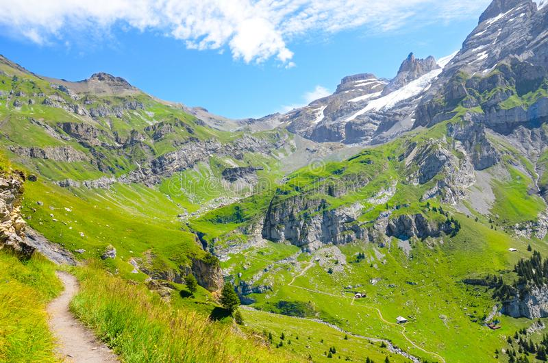 Beautiful Alpine landscape photographed in summer season. Hiking path surrounded by rocks, mountains and green pastures. Swiss stock photography