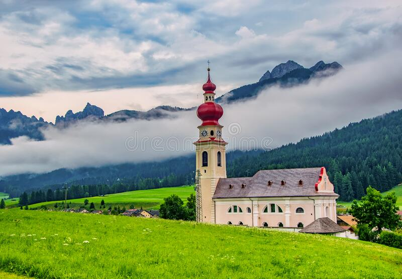 Beautiful alpine scenery of Vallabassa town with St. Stephen& x27;s church, Dolomite Alps, Italy. Beautiful alpine scenery of Vallabassa town with green meadow royalty free stock photos
