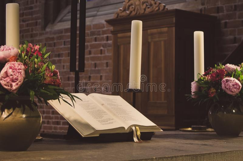 Beautiful altar in catholic cathedral faded. Open holy bible with flowers, candles and cross. Elegant decoration of church. Beautiful altar in catholic royalty free stock images