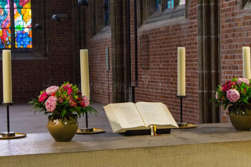 Beautiful altar in catholic cathedral. Open holy bible with flowers, candles and cross. Elegant decoration of church. Beautiful altar in catholic cathedral royalty free stock image