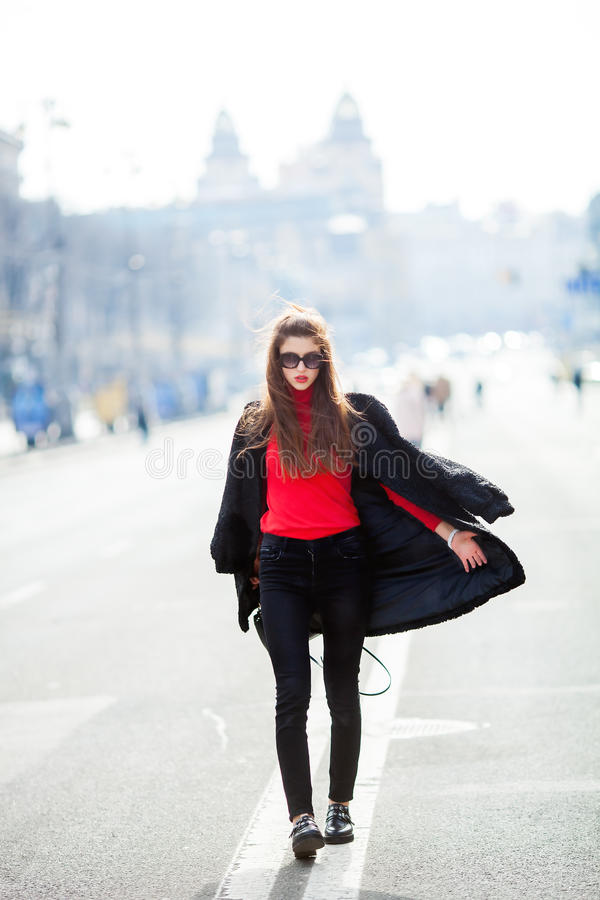 Beautiful amazing brunette woman with long wavy hairstyle in spring or fall stylish urban outfit walking on the street. Street fashion concept stock photo