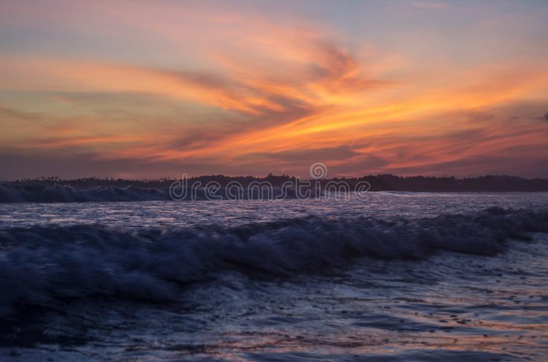 Beautiful amazing seascape of the ocean under orange sunset sky at Weligama bay stock photo