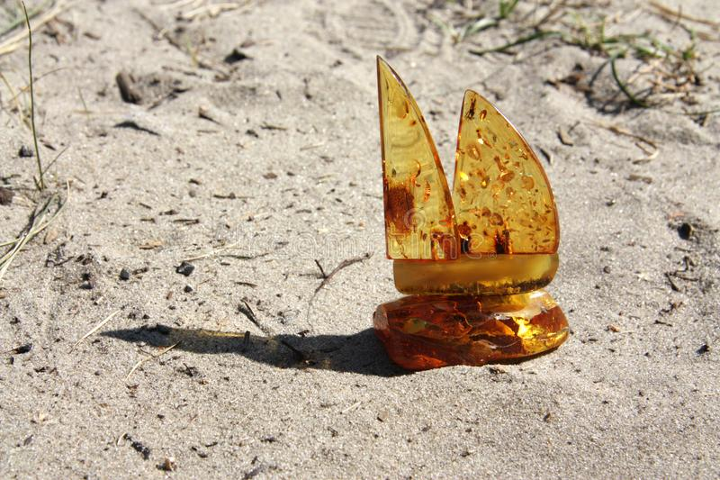 Beautiful amber boat sparkles in the sun. Beautiful amber boat floats on a sand dune and sparkles in the sun stock images