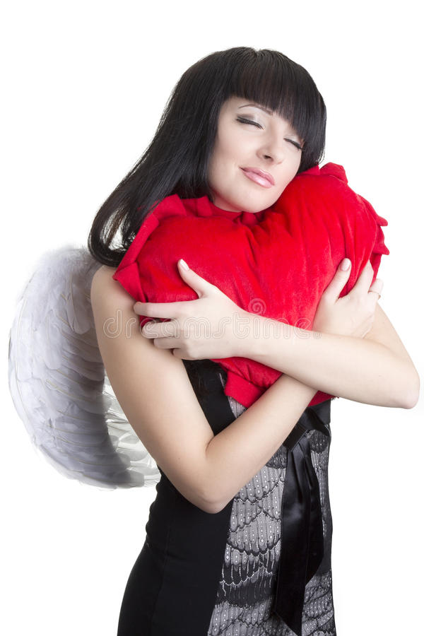 Beautiful angel woman embracing red heart stock image