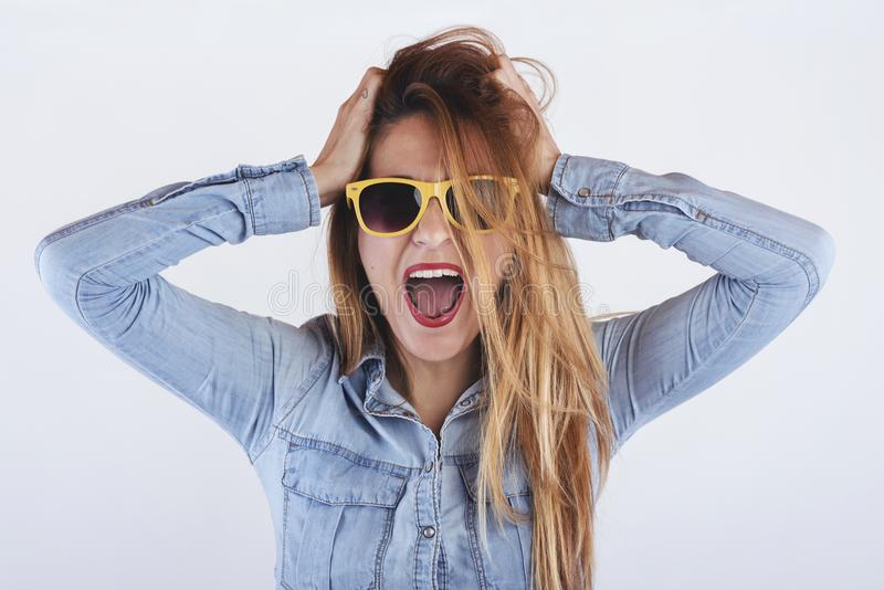Beautiful angry woman. With yellow glasses royalty free stock image