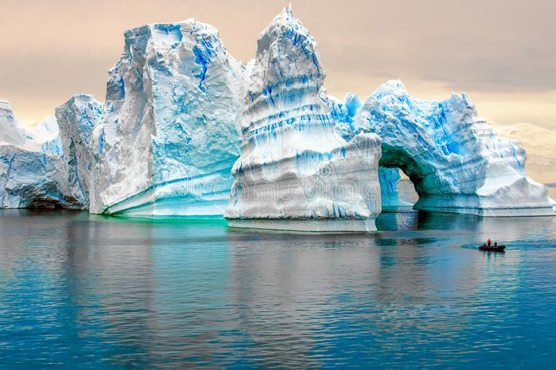 Iceberg in Antarctic, Ice Castle with Zodiac in Front, Iceberg sculptured like fairytale castle. Beautiful antarctic ice-architecture with zodiac in front