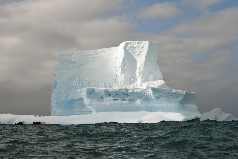 Huge antarctic table iceberg with zodiac in front. Small boat with people in front of Iceberg royalty free stock images