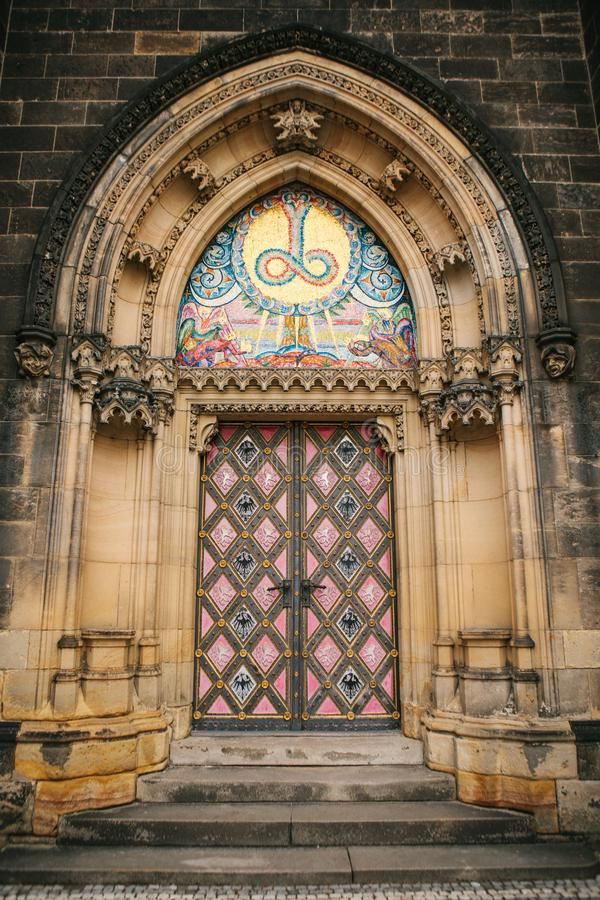 A beautiful antique door to the Catholic cathedral located in the High City called Vysehrad in Prague. Entrance to the stock photos