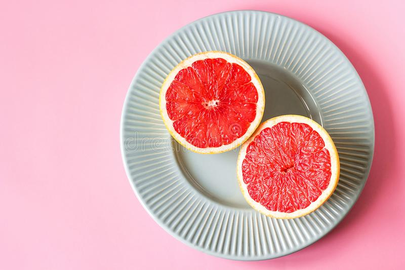 Beautiful appetizer fresh red grapefruit citrus fruit with half slice on blue plate and pink background close up top view natural stock photography