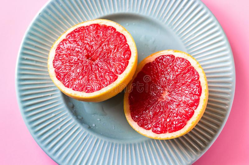 Beautiful appetizer fresh red grapefruit citrus fruit with half slice on blue plate and pink background close up top view natural stock images