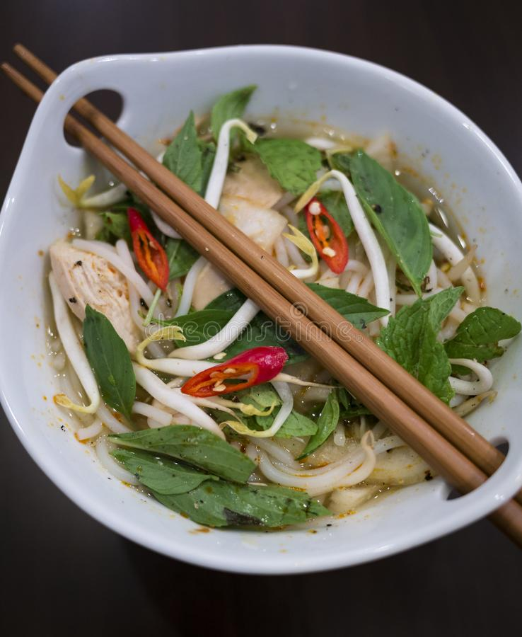 Beautiful and appetizing photo of a traditional vietnamese chicken noodle soup, also know as Pho Ga. In a white bowl with wooden b stock photography