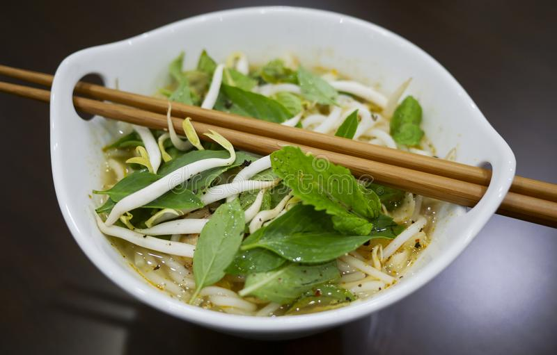 Beautiful and appetizing photo of a traditional vietnamese chicken noodle soup, also know as Pho Ga. In a white bowl with wooden b stock image
