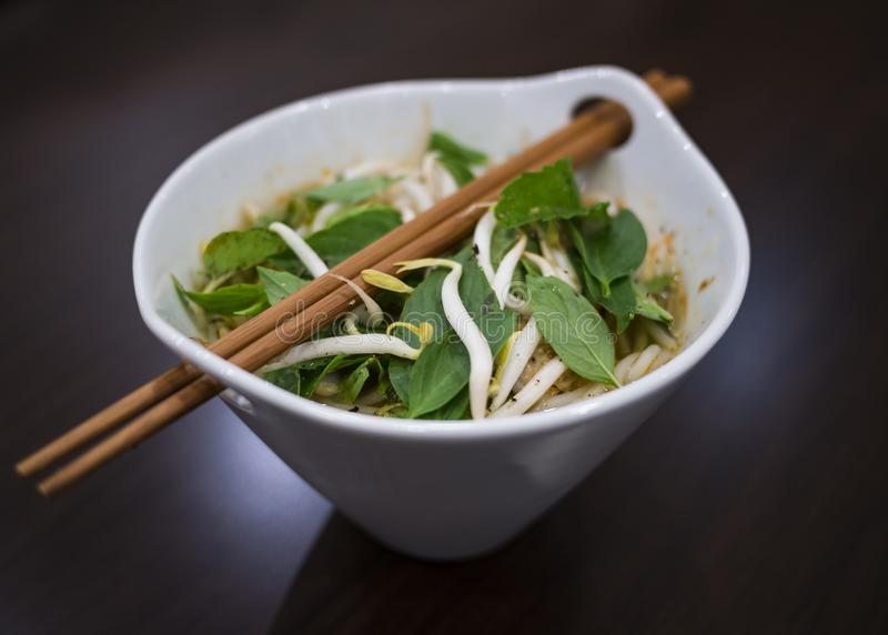 Beautiful and appetizing photo of a traditional vietnamese chicken noodle soup, also know as Pho Ga. In a white bowl with wooden b. Ackground and luxurious stock image