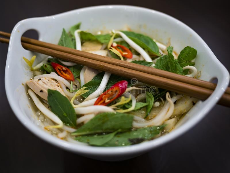 Beautiful and appetizing photo of a traditional vietnamese chicken noodle soup, also know as Pho Ga. In a white bowl with wooden b. Ackground and luxurious royalty free stock photography