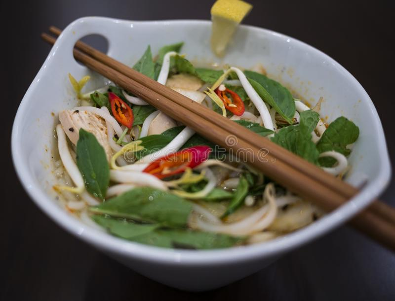 Beautiful and appetizing photo of a traditional vietnamese chicken noodle soup, also know as Pho Ga. In a white bowl with wooden b. Ackground and luxurious royalty free stock photo