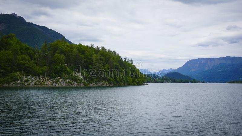 Beautiful Alps landscape with lake surrounded by green mountains, valley  and forest royalty free stock image
