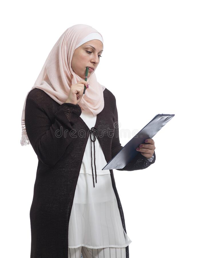 Beautiful Arab Muslim businesswoman thinking about a solution, dressed in traditional Islamic clothing stock image