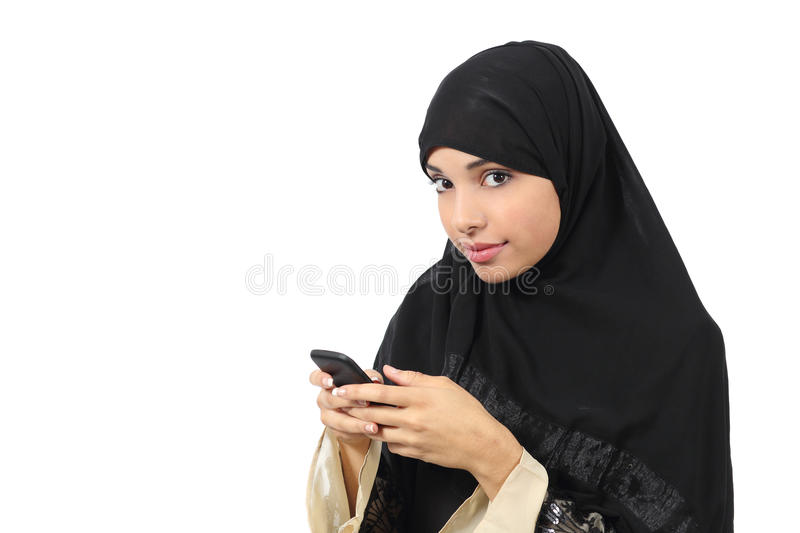 Beautiful arab woman browsing her smart phone and looking to the camera royalty free stock photography