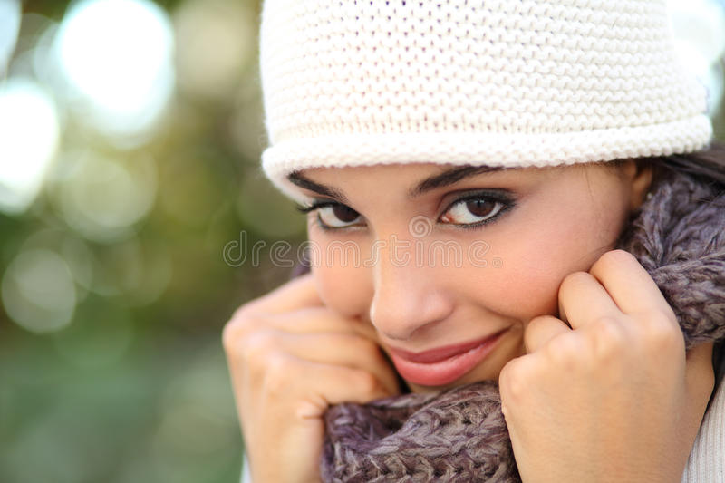 Beautiful arab woman portrait warmly clothed. With an unfocused green background royalty free stock photos