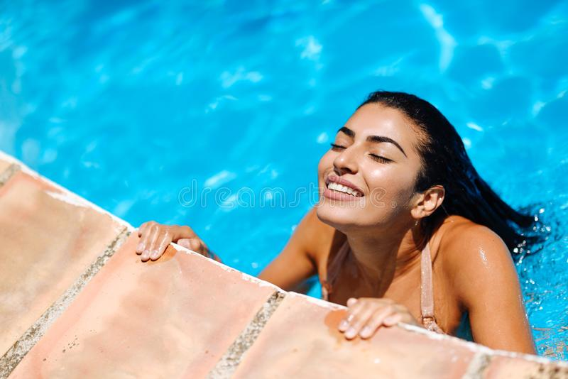 Beautiful Arab woman relaxing in swimming pool. royalty free stock photos