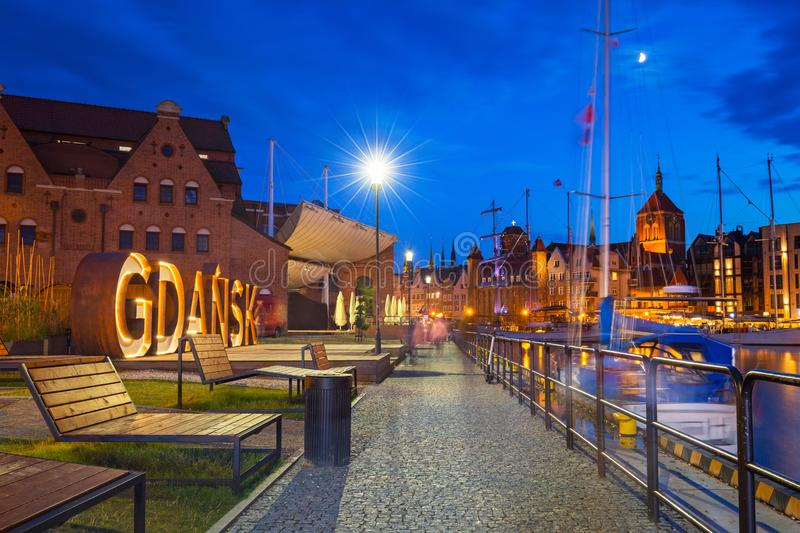 Beautiful architecture of Gdansk with an outdoor sign at dusk, Poland. City, symbol, night, europe, street, sidewalk, island, logo, olowianka, sky, travel royalty free stock photography