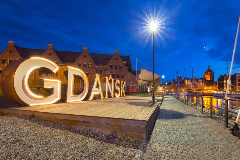Beautiful architecture of Gdansk with an outdoor sign at dusk, Poland. City, symbol, night, europe, street, sidewalk, island, logo, olowianka, sky, travel stock images