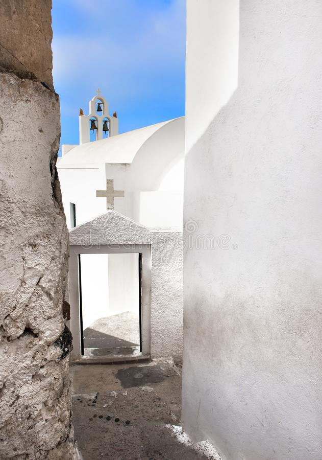 Beautiful architecture of Santorini, Greece. Whitewashed walls of houses and blue and white churches and belltowers against blue sky in the background, perfect royalty free stock photography