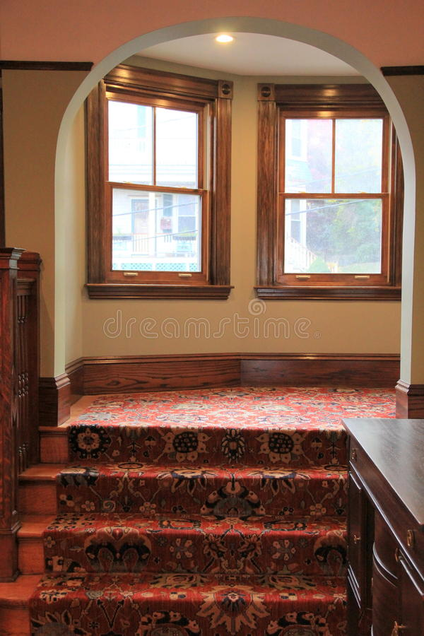 Beautiful archway, with warm wood and carpeting in home. Warm and welcoming foyer of home, with pretty archway that leads up carpeted wood staircase stock images