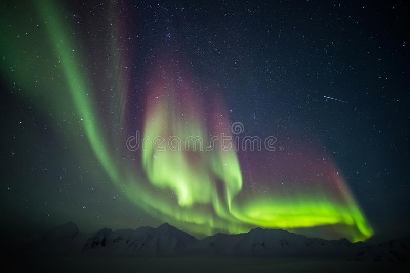 Beautiful Arctic mountain landscape with Northern Lights - Spitsbergen, Svalbard. Natural phenomenon of Northern Lights (Aurora Borealis) related to the earth's