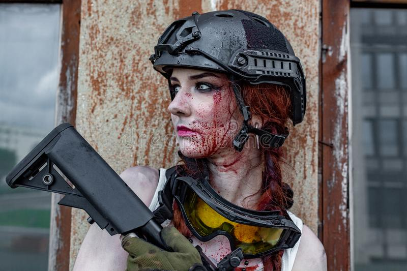 Beautiful army girl with a bloody face with rifle in camouflage clothes in urban scene, getting rest. portrait, close up. Beautiful army girl with a bloody face stock photography