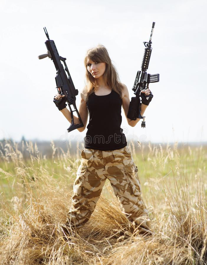 Beautiful army girl  with machine guns in the hands. Beautiful army girl  with machine guns in the. Beautiful army girl with gun  outdoor, adult, armed, armor stock photos
