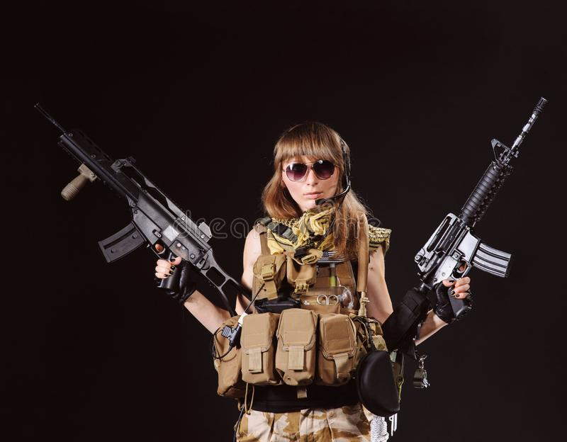 Beautiful army girl with machine guns in the hands isolated on the black background. Isolated over black background, adult, armed, armor, attractive, battle stock images