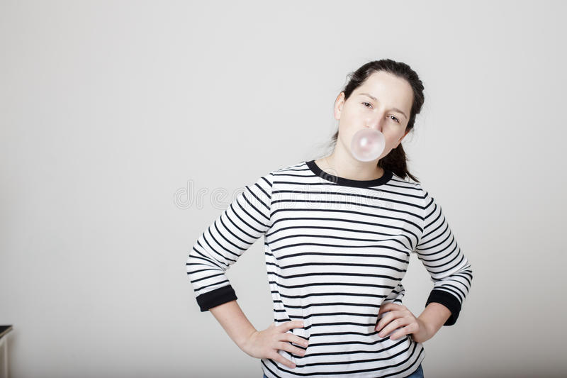Beautiful arrogant woman inflates pink bubbles of gum. Hands on hips and looking frame, dressed in a striped sweater royalty free stock photos