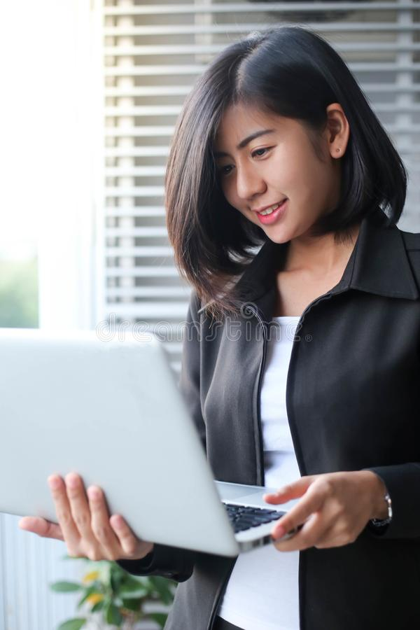 Beautiful asia business woman smiling and holding laptop with of stock photo