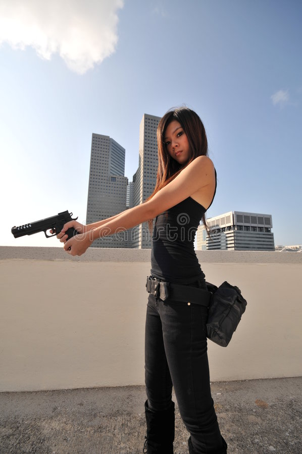 Beautiful Asian Agent/ Killer standing on the roof royalty free stock photo