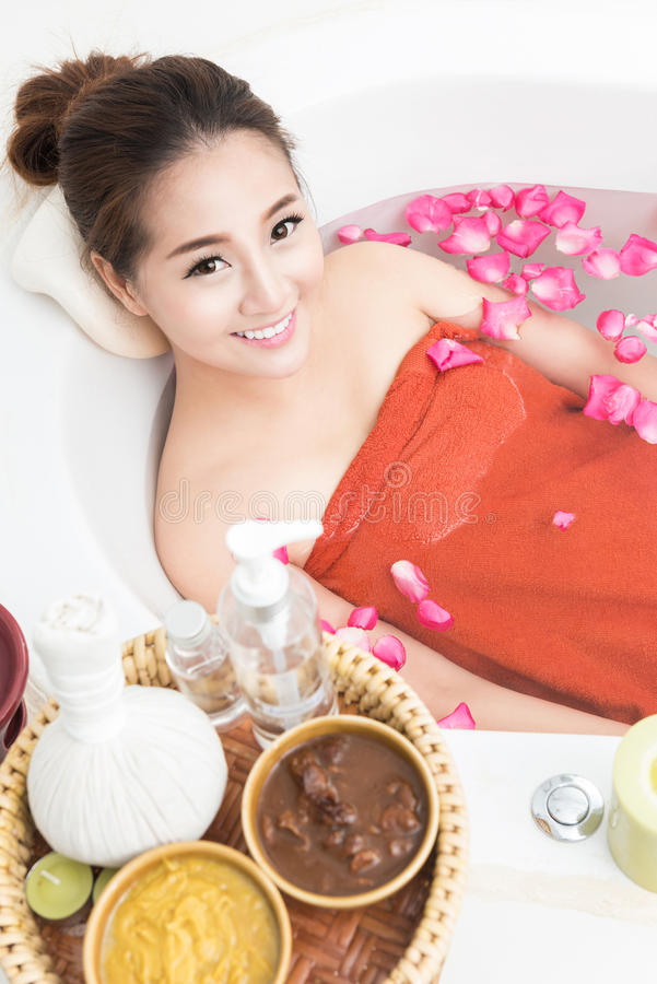 Beautiful Asian beauty woman in bath with rose petal. body care and Spa royalty free stock photo