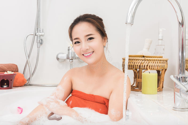 Beautiful Asian beauty woman in bath with rose petal. body care and Spa stock photography