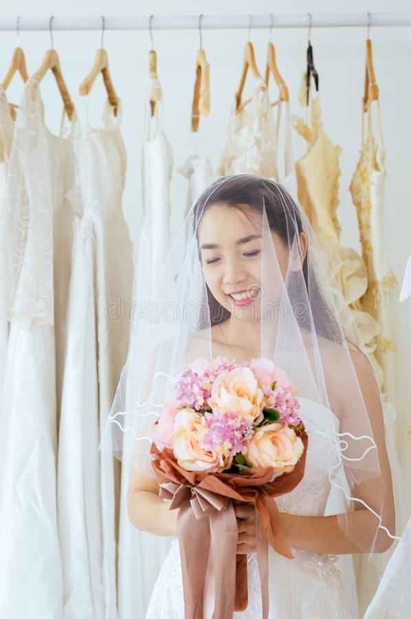 Beautiful asian bride woman holding a bouquet on hand for wedding with felling shy,Romantic and sweet moment royalty free stock photography