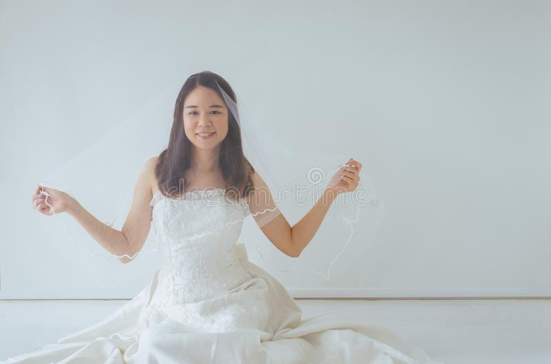 Beautiful asian bride woman in white dress hands holding flower with feeling Happy and funny stock photography